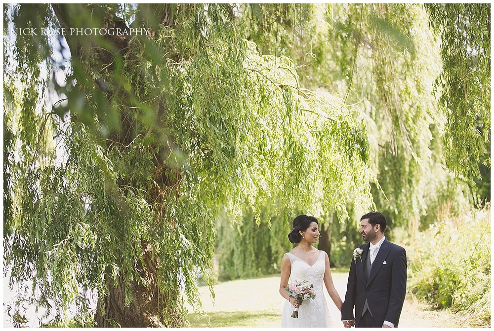 Bride and groom wedding portrait photograph under a willow tree at Hever Castle Kent