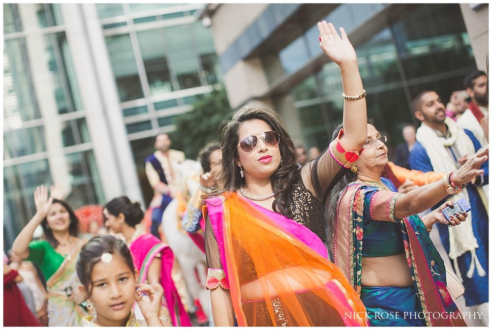 Indian wedding guests dancing during the groom's Baraat Hindu wedding entrance in London