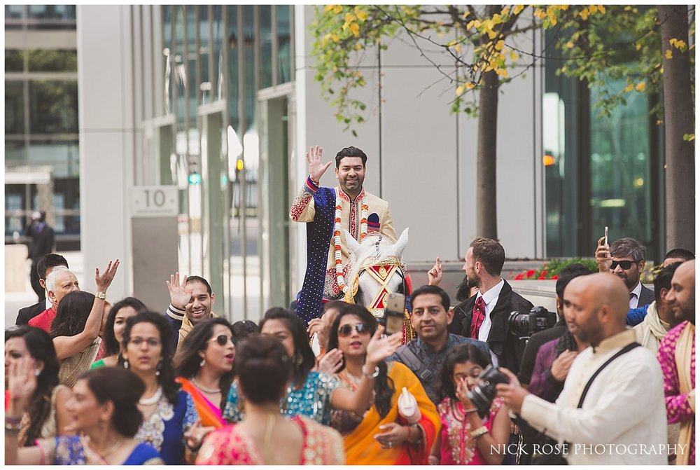 Hindu Baraat and the groom's Indian wedding entrance on a horse in Canary Wharf London