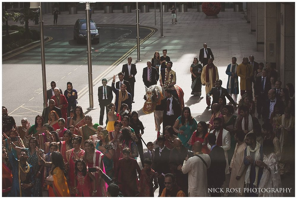 Colourful hindu Baraat wedding entrance with the Indian groom on a horse in Canary Wharf