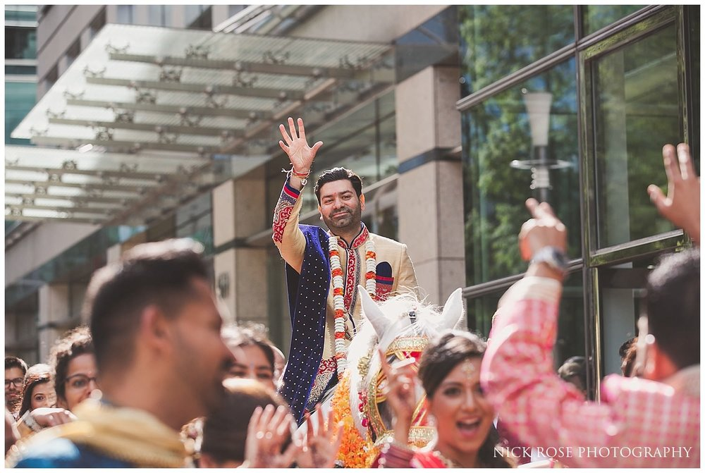 Groom on a hindu horse with his hands in the air for his Indian Baraat entrance in London