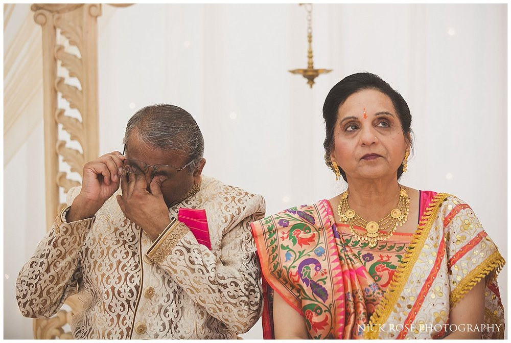 Father of the bride crying during his daughters wedding entrance at East Wintergarden Hindu wedding in Canary Wharf London