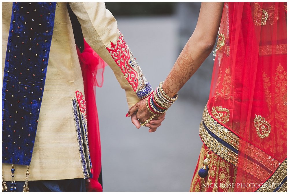 Asian bride and groom holding hands in Canary Wharf London