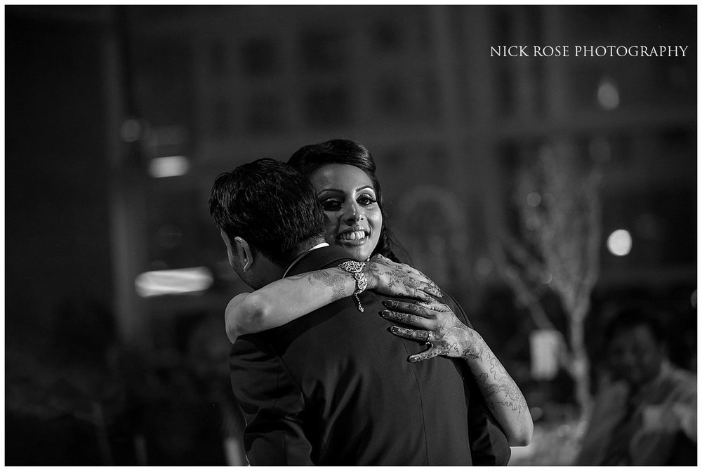 Bride and groom hug on the dance floor at a Hindu wedding reception in East Wintergarden Canary Wharf London