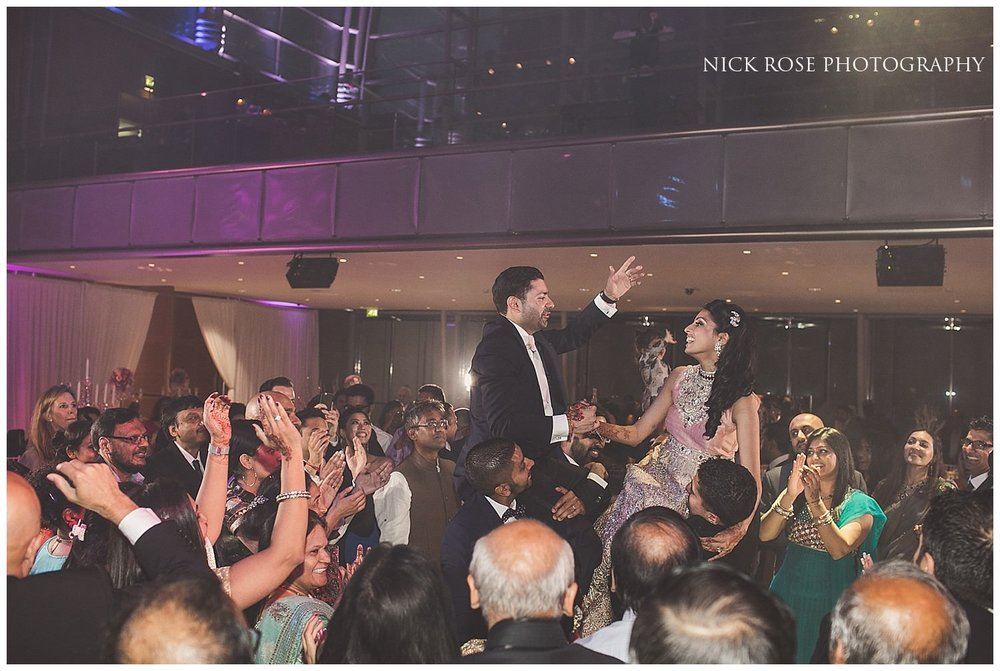 Bride and groom raised onto guests shoulders during an Indian wedding reception in East Wintergarden Canary Wharf London