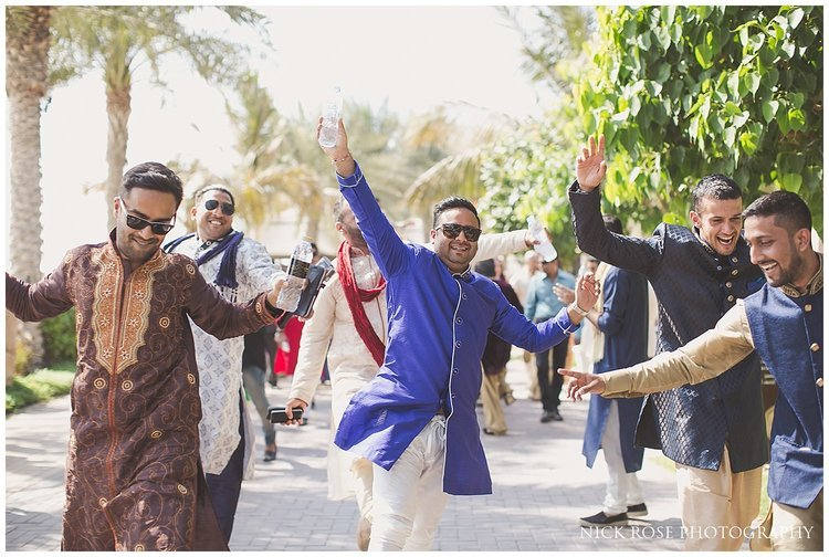 Groom's friends dancing into an Asian beach wedding in Dubai