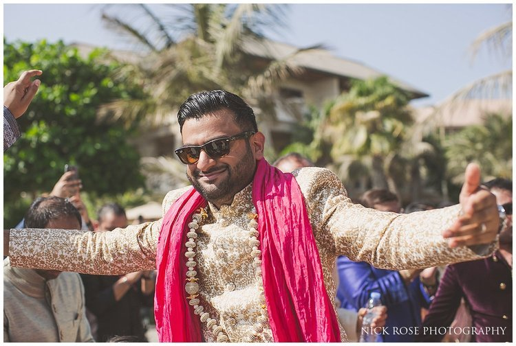 Indian groom wearing a pink scarf making his beach wedding ceremony entrance at the Sofitel Palm Dubai