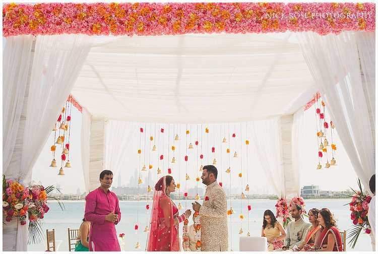 Bride and groom standing under a Hindu wedding mandap exchanging garlands at the Sofitel Palm Dubai