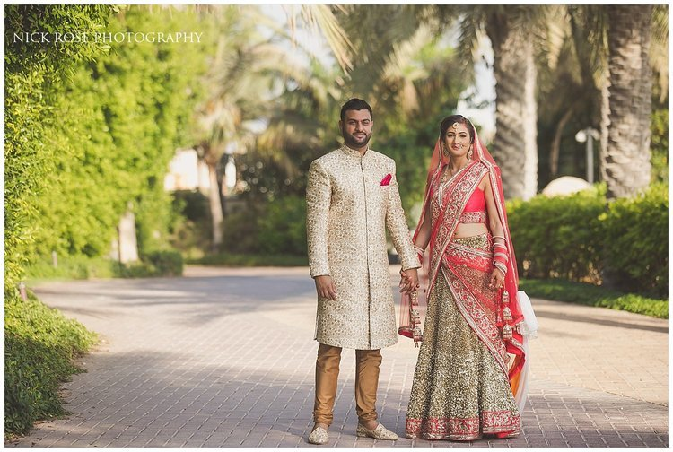 Indian bride and groom holding hands at the Sofitel Palm Dubai