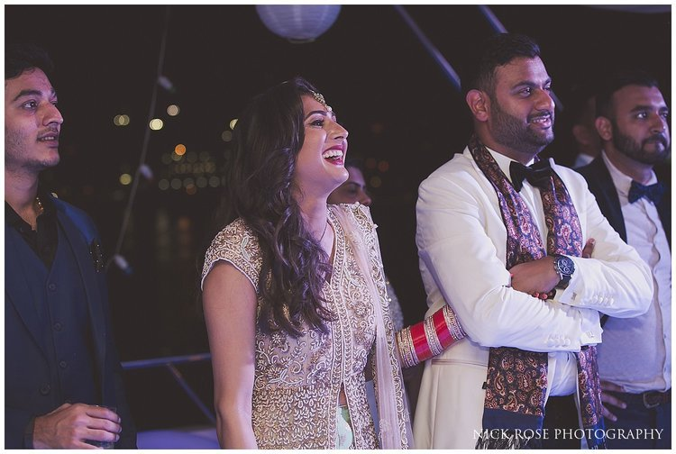 Bride and groom laughing during wedding speeches in Dubai