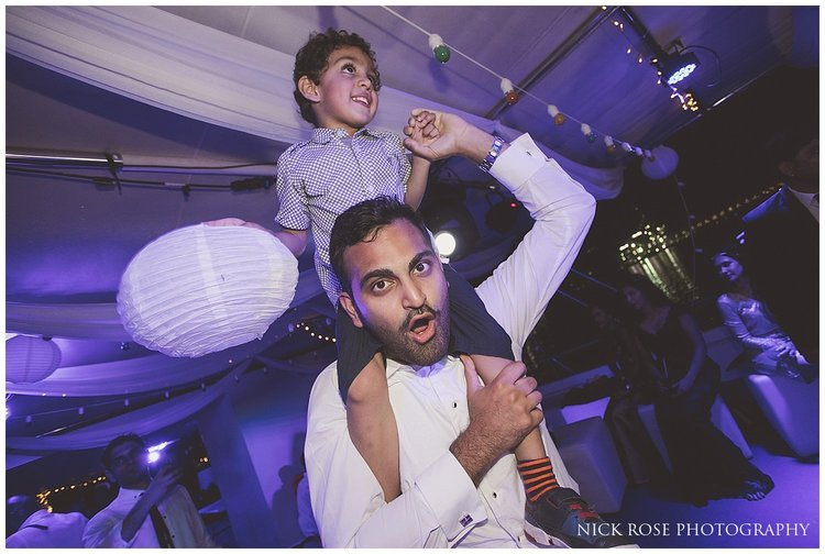 Boy dancing on a mans shoulders during a destination Dubai wedding