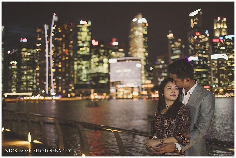 Pre wedding photograph of a couple standing in front of the skyscrapers at Marina bay in Singapore at night