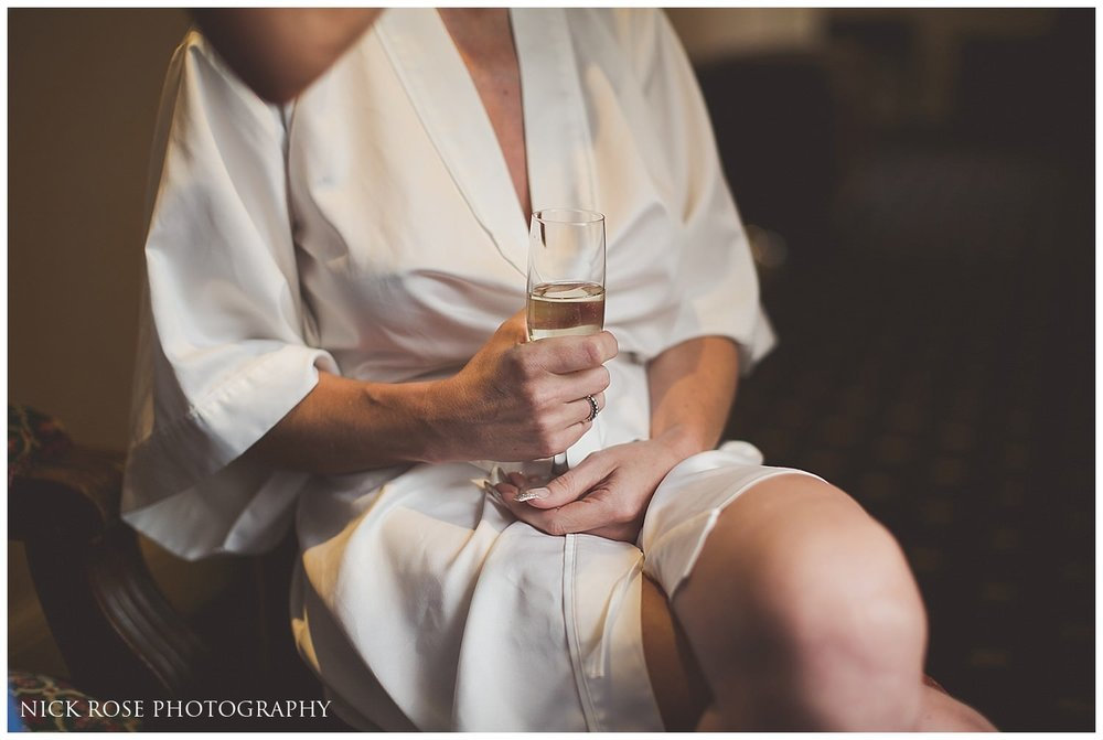 Bride sitting in a chair with a glass of champagne