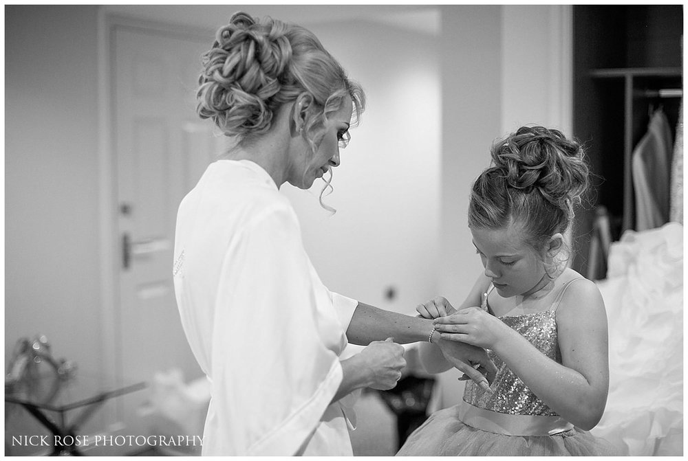 Brides daughter putting a bracelet on the bride before a wedding ceremony at St Mary's Church in Tickhill