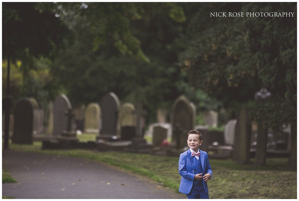 Boy in blue suit standing outside St Mary's church in Tickhill before a wedding