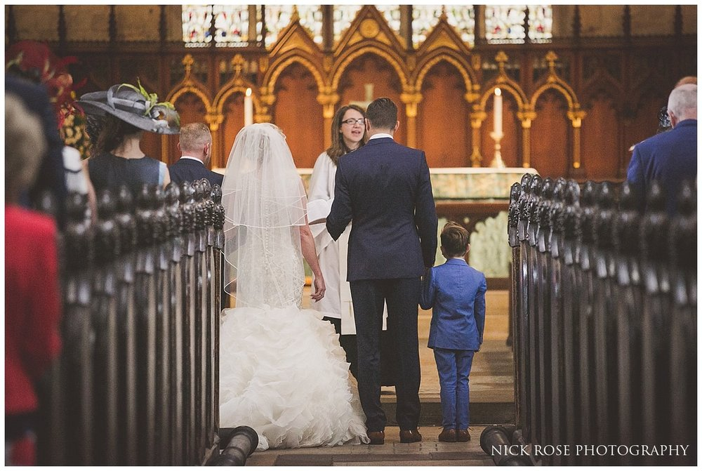 Bride and groom with son holding hands during a Tickhill wedding ceremony at St Mary's church in Yorkshire