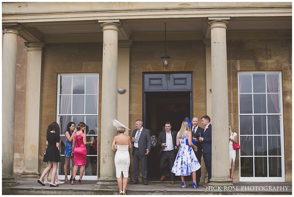 Guests standing outside under the columns for a Rudding Park wedding in Harrogate
