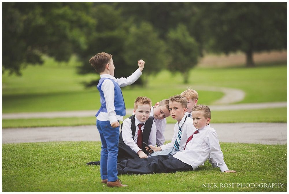 Young boys sitting outside on the grass during a Rudding Park Hotel wedding in Harrogate