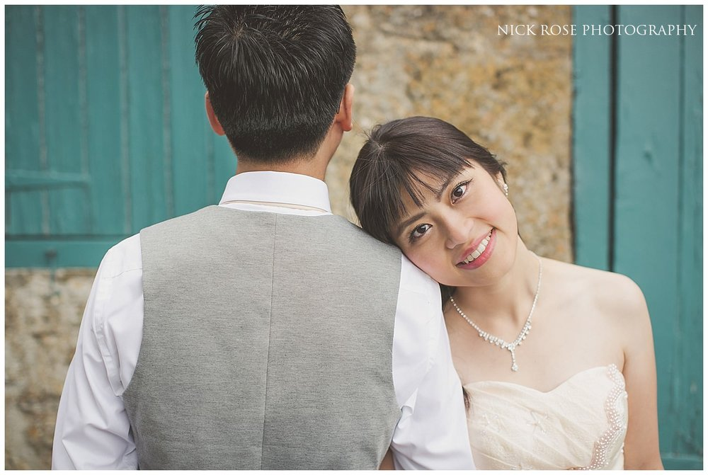 Bride resting her head on pre wedding groom's shoulders in front of a green barn door in the Cotswolds