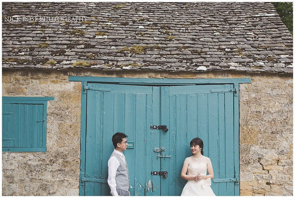 Pre wedding photograph of a couple in front of a green Cotswolds barn in Stanton