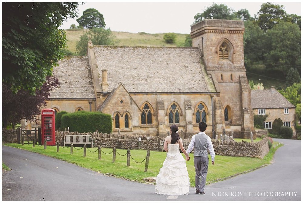 Pre wedding photograph of a couple walking towards and church and red phone box in the cotswolds
