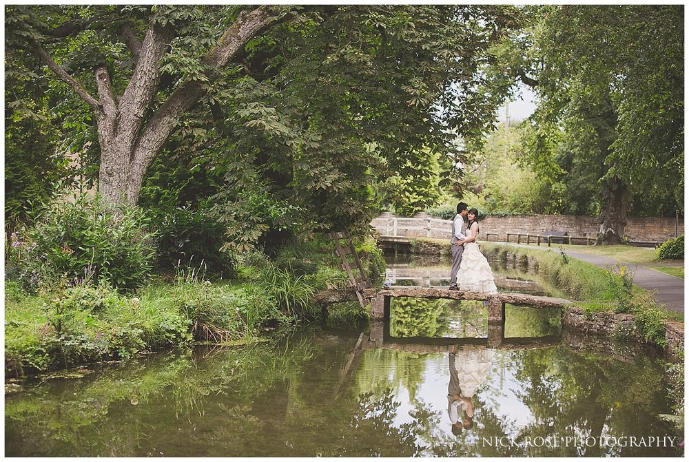 Reflection in a stream of a bride and groom in a wedding dress and suit during a pre wedding photography session in Lower Slaughter
