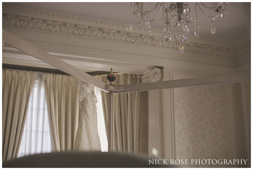 White wedding dress hanging on a four poster bed at Hedsor House in Buckinghamshire