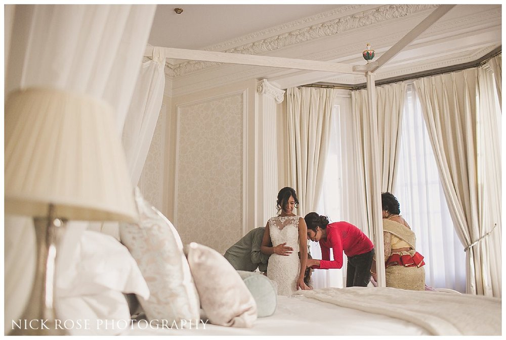 Bride putting on her wedding dress for a Hedsor House in Buckinghamshire