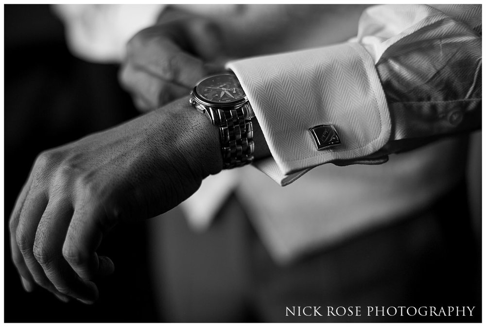 Groom putting on his cufflinks before a Hedsor House wedding