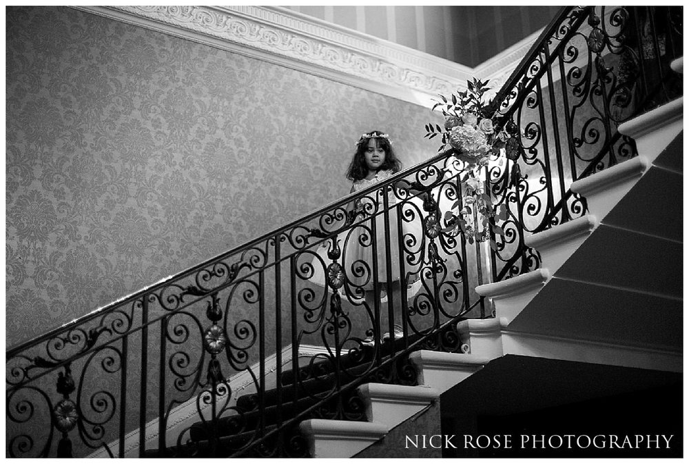 Flower girl and bridesmaid coming down stairs at Hedsor House in Bucks