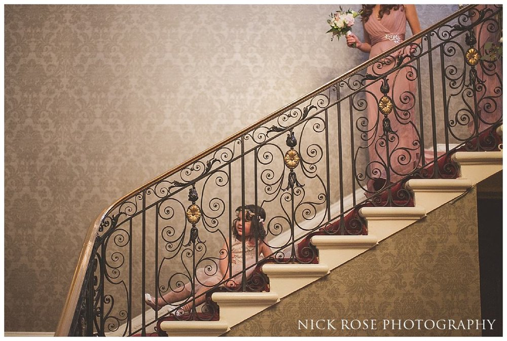 Flower girl bumping down the stairs before wedding ceremony at Hedsor House in Taplow