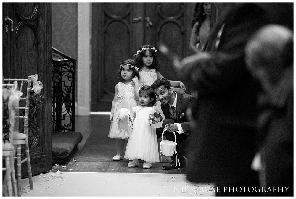 Flower girl walking up the Isle in the Centre Hall for a Hedsor House wedding in Buckinghamshire