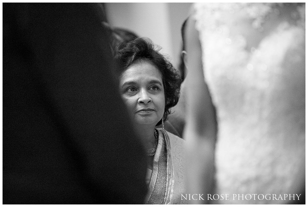 Mother of the bride looking at the couple during a wedding ceremony in the centre Hall in Buckinghamshire