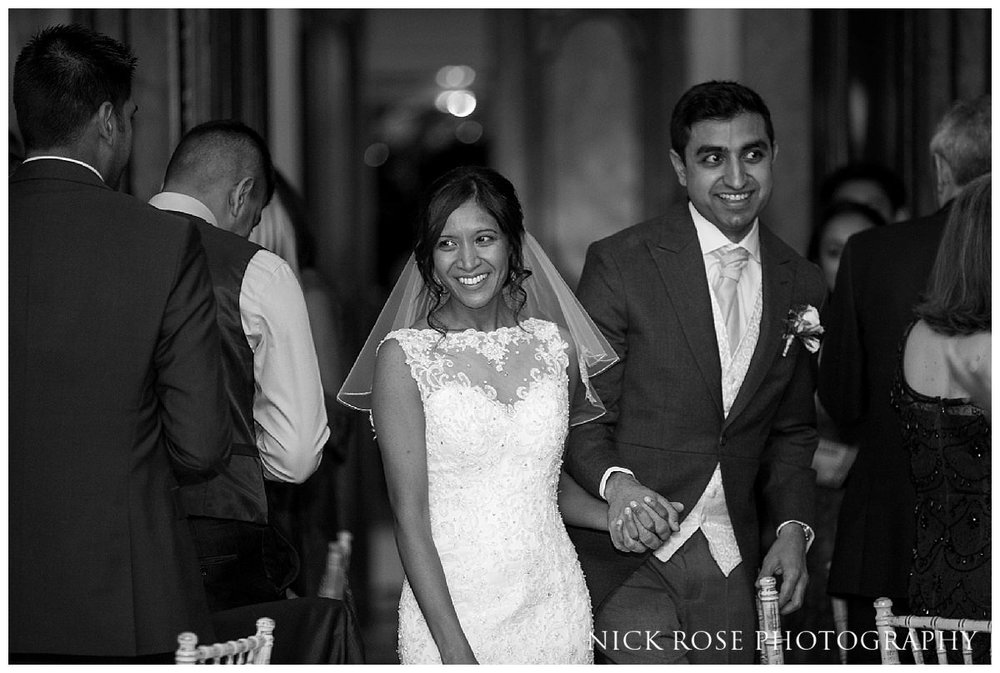 Bride and groom holding hands and entering the wedding reception at Hedsor House wedding in Buckinghamshire