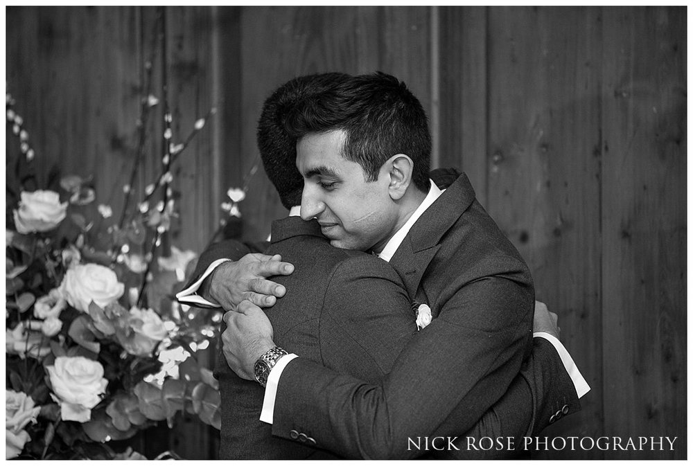Groom and best man hugging at a Hedsor House wedding in Buckinghamshire