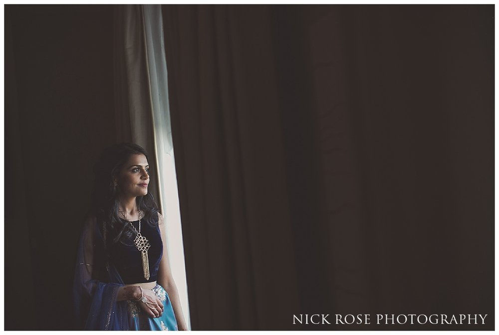 Indian bride getting ready and looking out of the window at The Grove in Watford, Hertfordshire