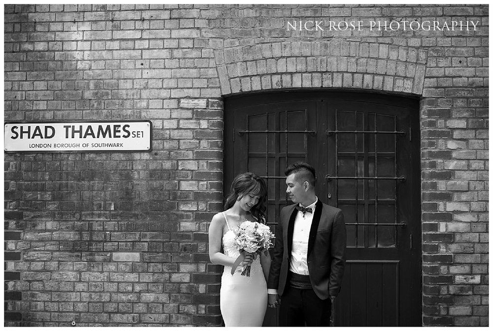 Pre wedding couple standing in front of a warehouse doorway at Shad Thames in London