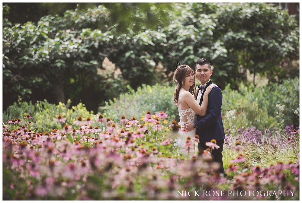 Pre wedding couple standing amongst flowers in Potter's Fields next to Tower Bridge in London