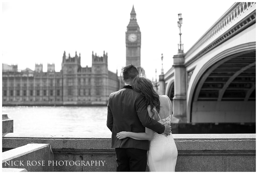 Couple looking across the River Thames at Big Ben during a pre wedding photography shoot in London