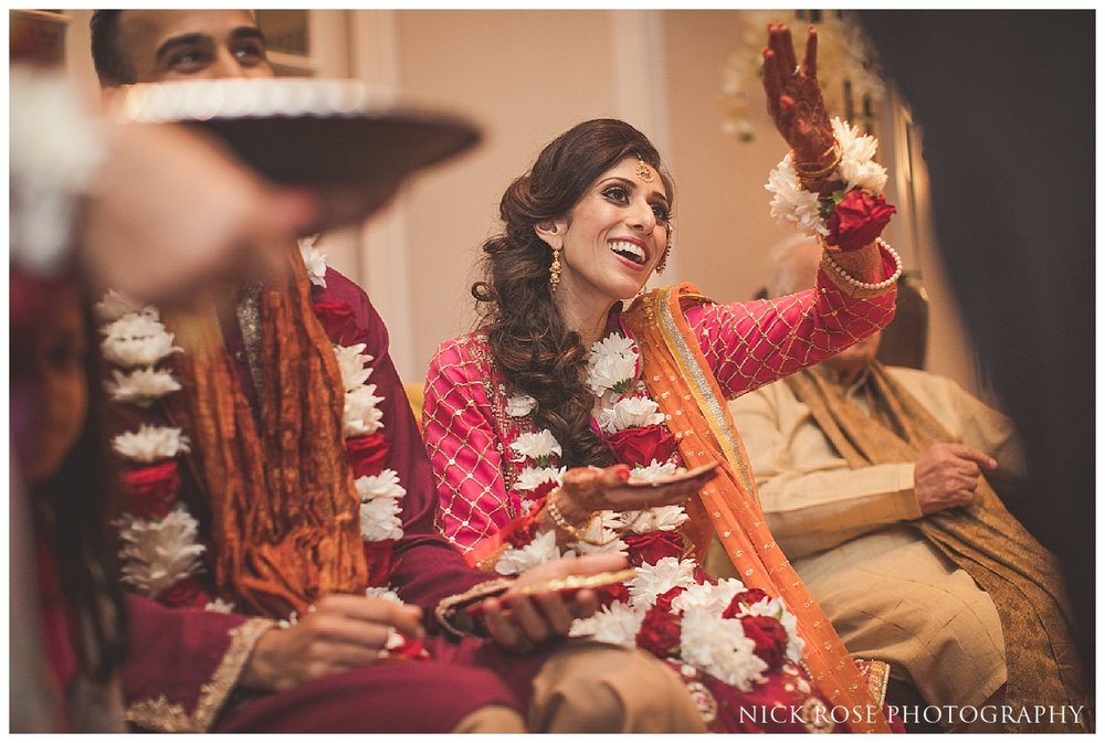 Garlands being placed around bride and groom during a Pakistani wedding mehndi at the Sheraton Grand in Park Lane