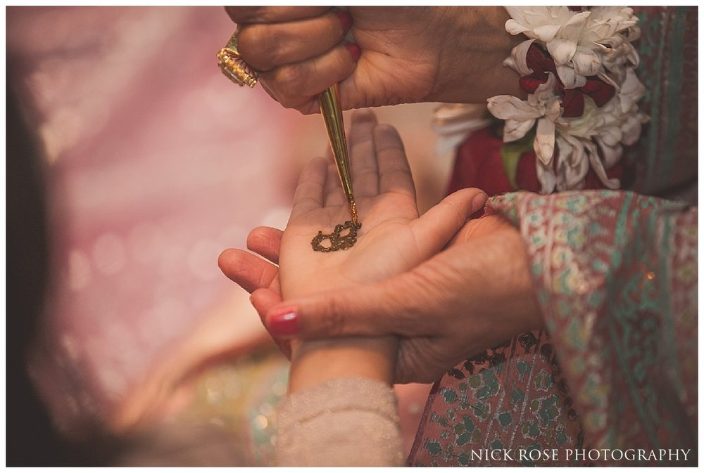 Henna being put on guests hands during a Pakistani wedding event at the Sheraton Grand in Park Lane