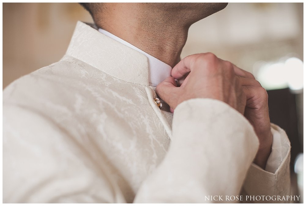 Groom putting on his jacket before a Pakistani Wedding at the Ritz Hotel London