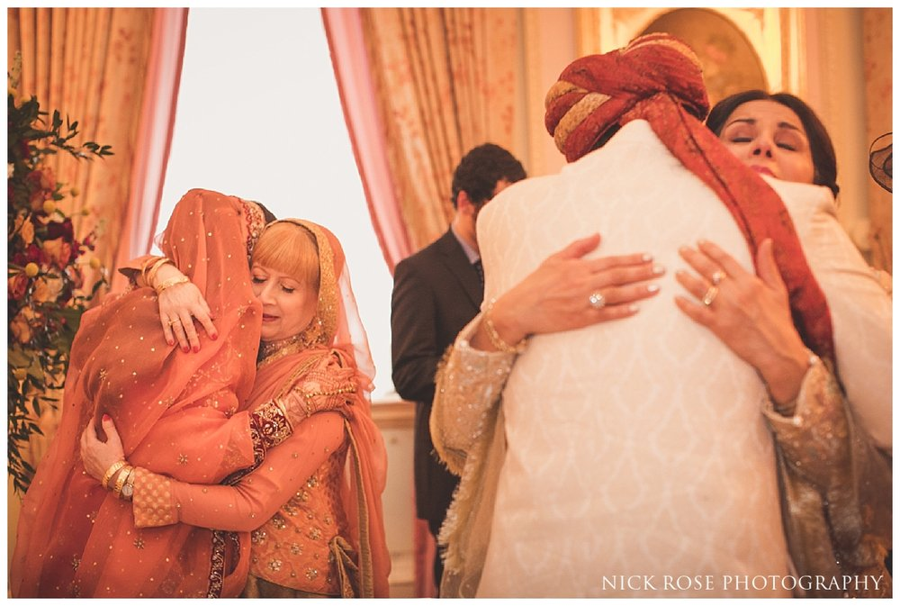 Parents hugging bride and groom following an Asian wedding ceremony at the Ritz in London