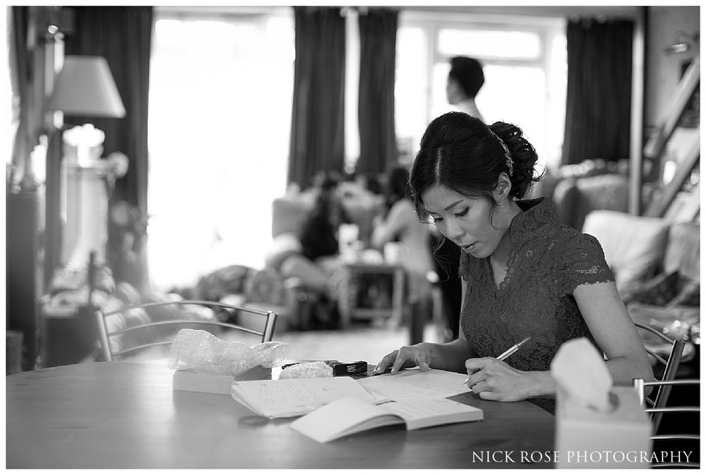 Bride writing her vows before a Hampton Court Place wedding at the Little Banqueting House in Surrey