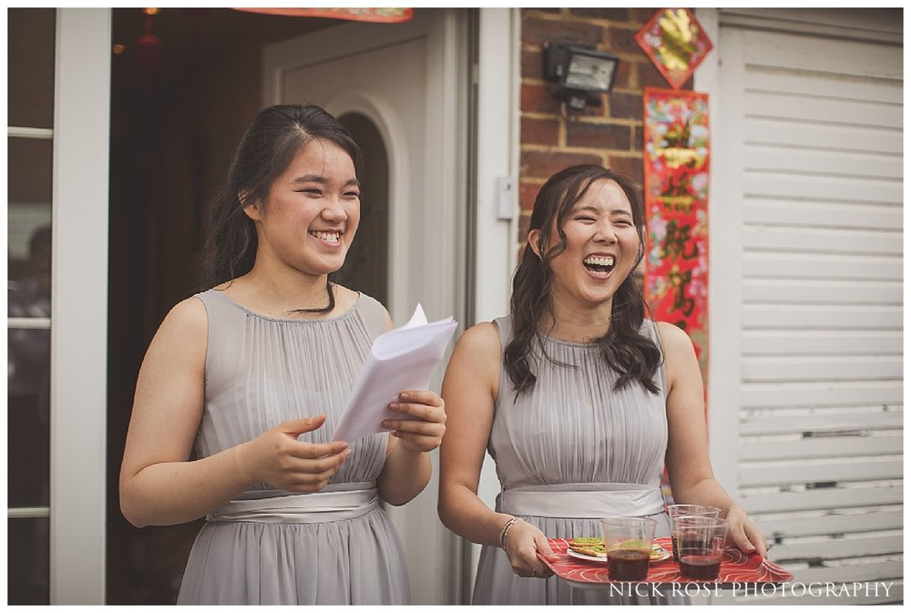 Asian bridesmaids reacting to gatecrashing games before a Hampton Court Place wedding at the Little Banqueting House in Surrey