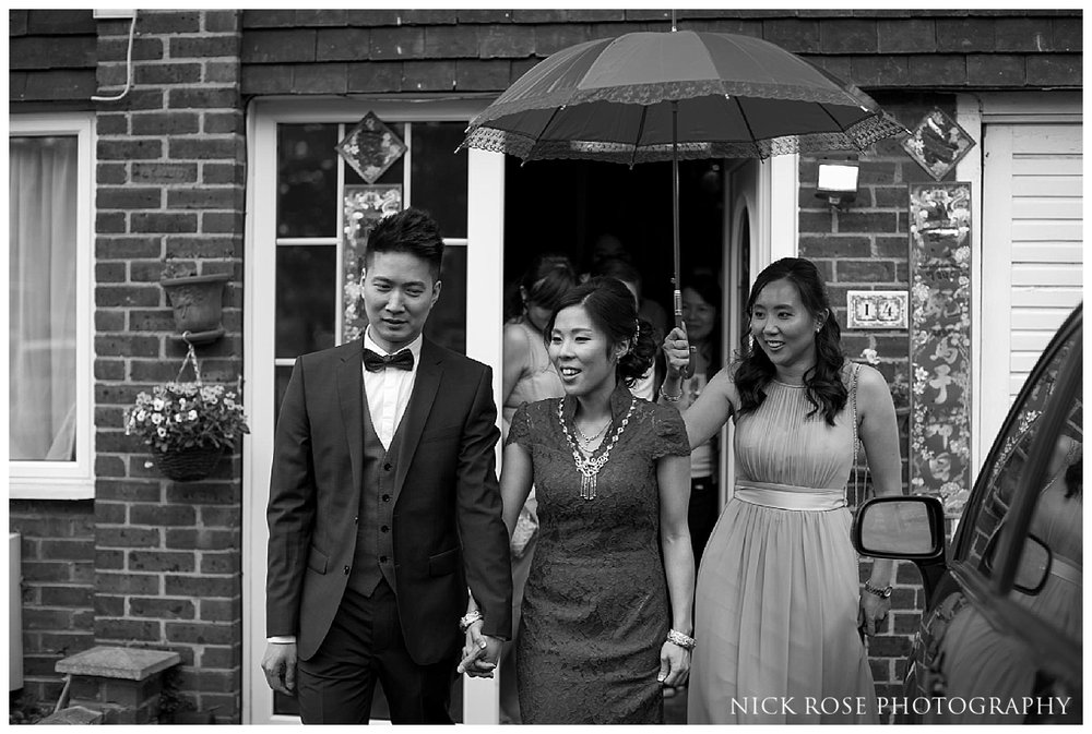 Bride and groom leaving house under a red umbrella before their London Chinese wedding