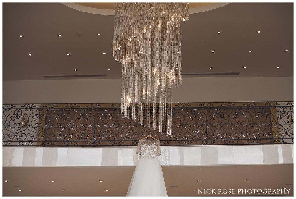 Wedding dress handing under chandelier for a Meridian Grand North London Wedding