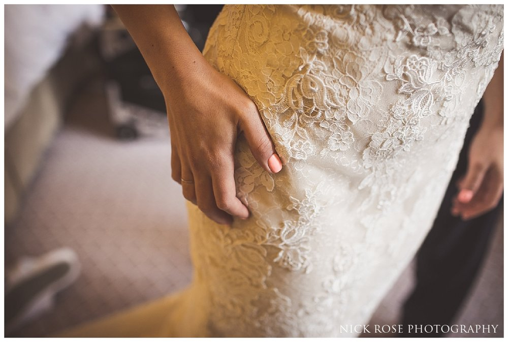 Bride putting on wedding dress for a central London wedding at Dartmouth House in Mayfair