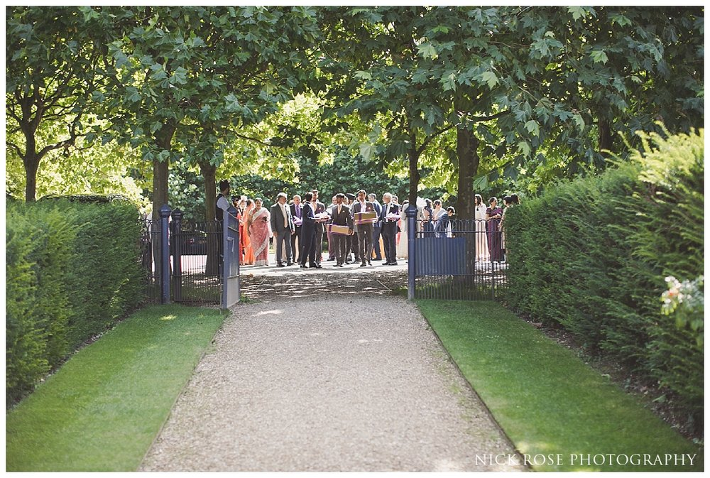 Guests arriving for an outdoor wedding reception at The Dairy in Waddesdon Manor Buckinghamshire