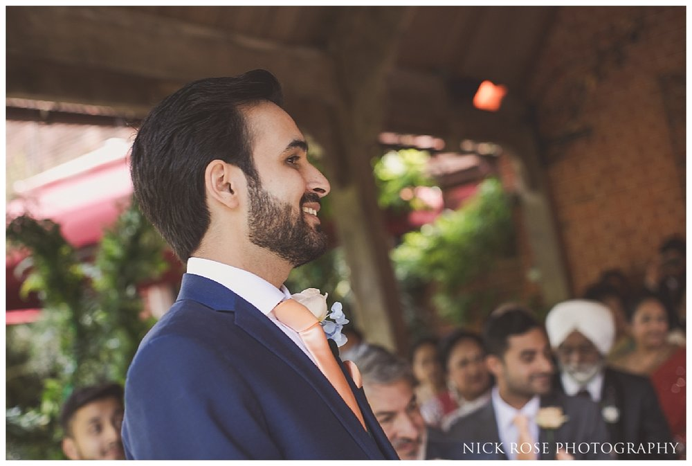 Groom watching bride walk down the isle for a Waddesdon Manor wedding